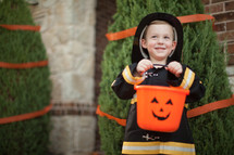 a boy child in a fire fighter costume trick-or-treating