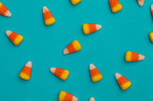 scattered candy corns on a blue background