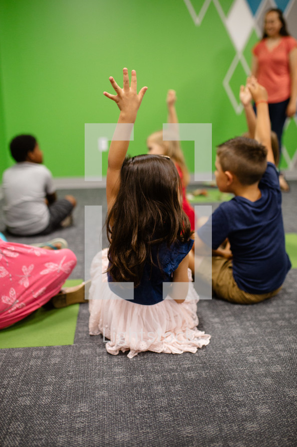 kids sitting on the floor of a classroom