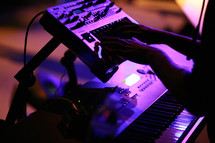 hands playing a keyboard at a concert