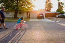 a father watching his daughter ride a bicycle