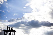 boys standing on a roof under a blue sky