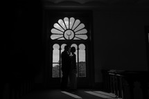 Silhouette of a man and woman standing before an ornate window.