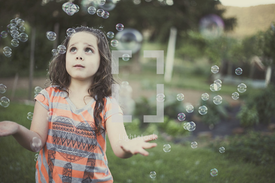 A little girl playing in bubbles