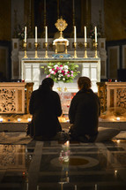 kneeling in prayer to God in front of an altar