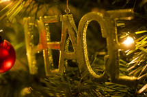 PEACE ornament hanging on a Christmas tree