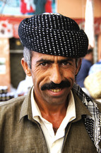Kurdish Man with moustache and beret with busy market place in background. [For more like this search Ethnic face]