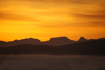sunset or sunrise over misty mountain range