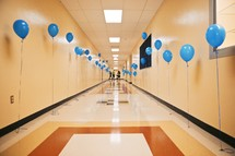 A hallway lined with blue balloons.