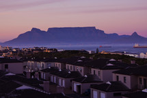 Houses overlooking mountain range at dawn sea ships