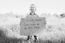 toddler boy holding a sign with the words I am fully healed, God helps me do BIG things