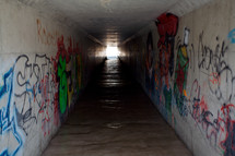 A long tunnel covered in graffiti.