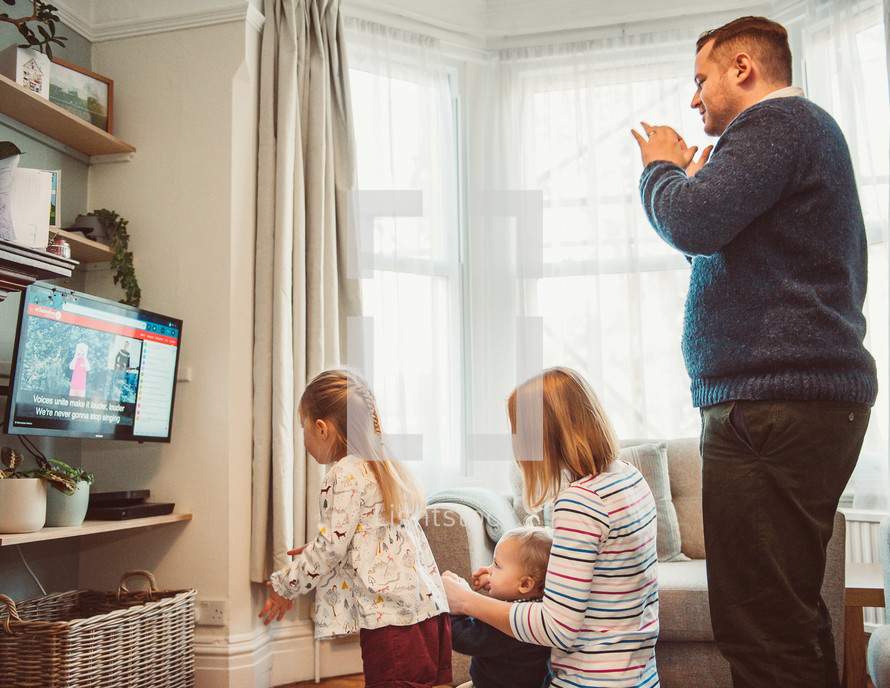 family clapping to music watching an online worship service
