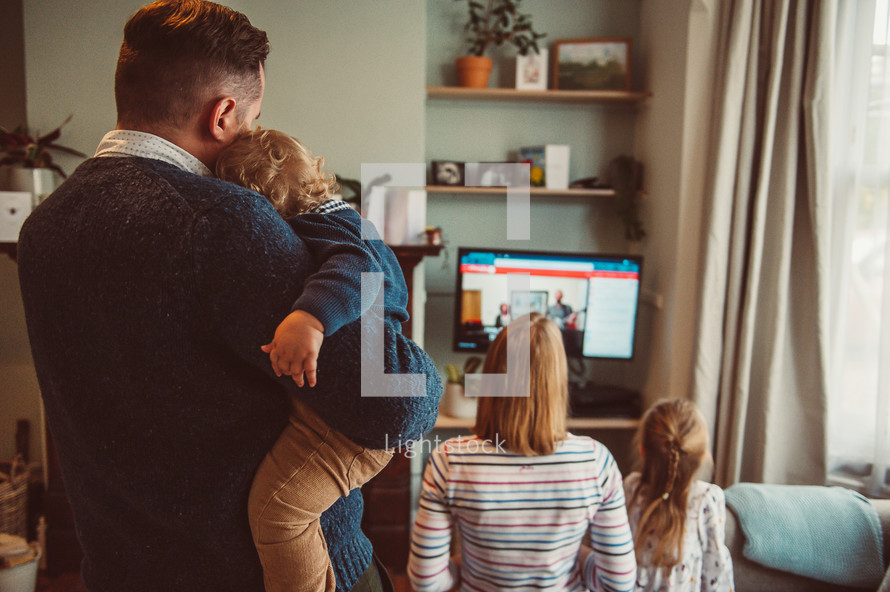 a family watching a worship service at home on their TV