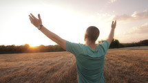 Man in field worshipping at sunrise