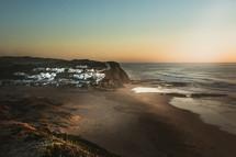 shore and coastal town at sunset
