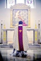 priest kneeling in prayer in front of an altar