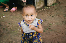 toddler girl in a dirt in a village