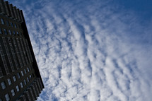 Ground view of side of tall building with cloud formations and blue sky in the background.