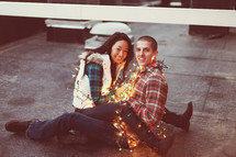 Happy couple wrapped in Christmas lights