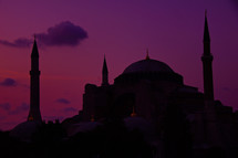 silhouette of a mosque under a purple sky