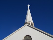 White Cross on a church steeple against a clear blue sky