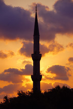 silhouette of a tower on a mosque at sunset