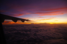 Airplane wing over clouds at sunset, sunrise, dusk, dawn