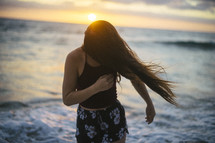 woman on a beach tossing her hair