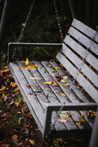 Autumn leaves falling on a bench swing.
