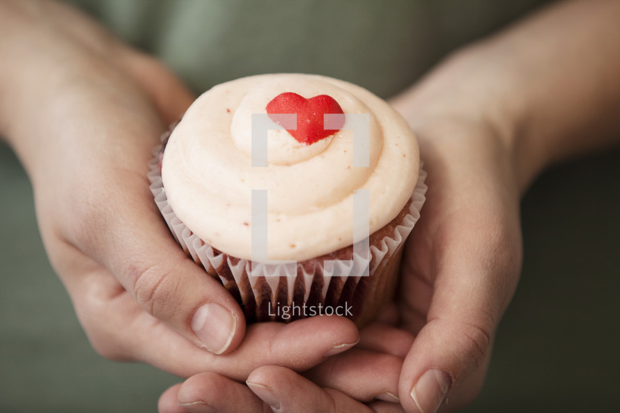 hands holding a Valentine's day cupcake