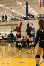 high school girls playing competitive volleyball