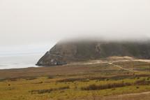 fog over a mountain peak along a shore