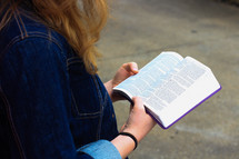 a teen girl in a jean jacket reading a Bible