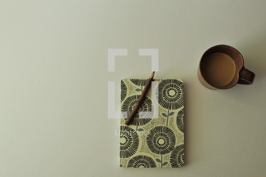 pencil on a journal and coffee mug