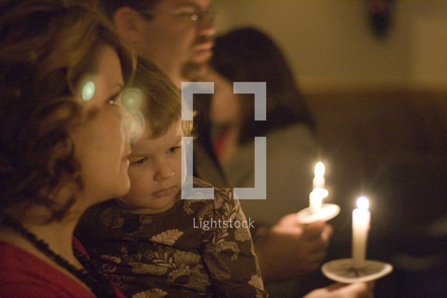 father, mother and child holding candles at a Christmas Eve church service
