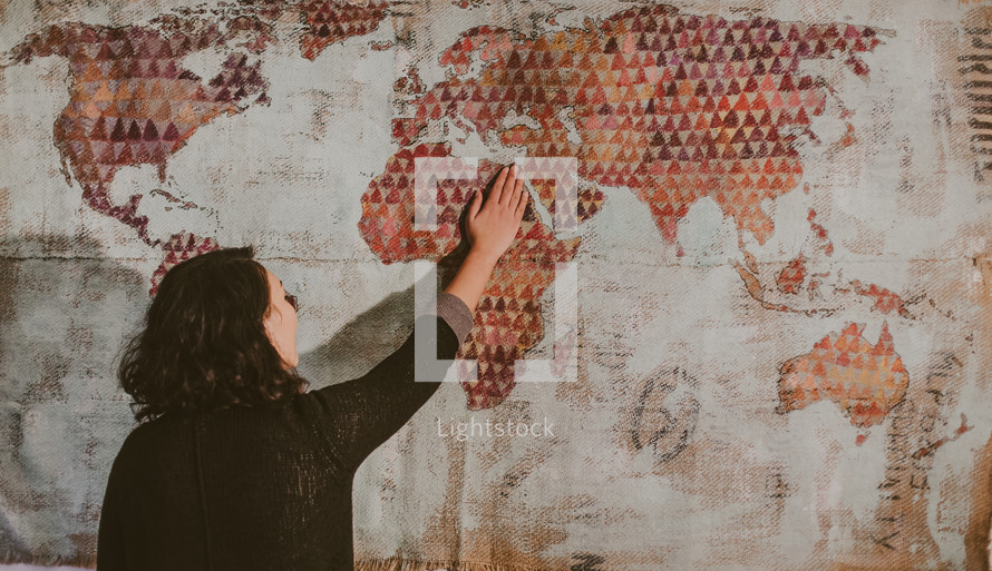 a woman with her hands on a world map