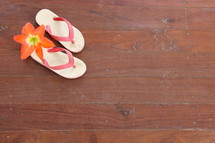 Child's flip flops on wooden floor with tropical flower orphan orphanage mission