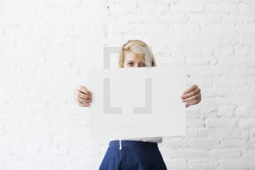 woman holding up a blank piece of paper