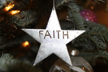 Star ornament with the word Faith hanging on a Christmas tree
