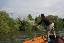 Fisherman casting a net from his boat