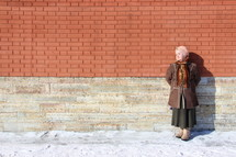 Russian woman leaning against a brick wall, warming herself in the sun