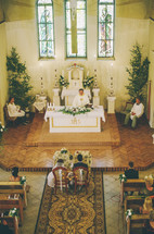 bride and groom sitting in chairs in front of the altar