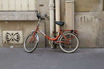 an old bike leaning against a concrete building
