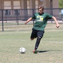 a teenage boy kicking a soccer ball