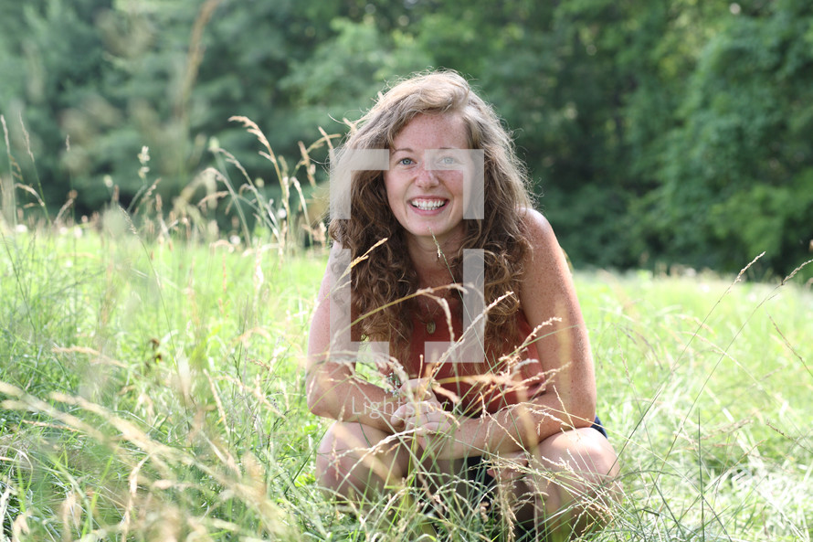 woman squatting in a field of tall grasses