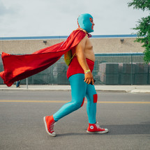 man walking down the street in a super hero costume