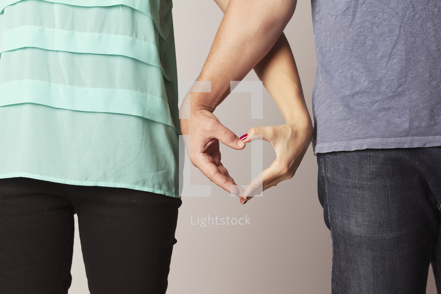 A couple making heart hands.