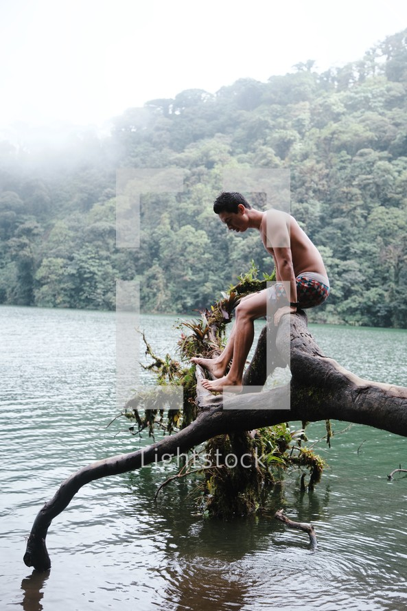 a man sitting on a fallen tree hanging over a lake