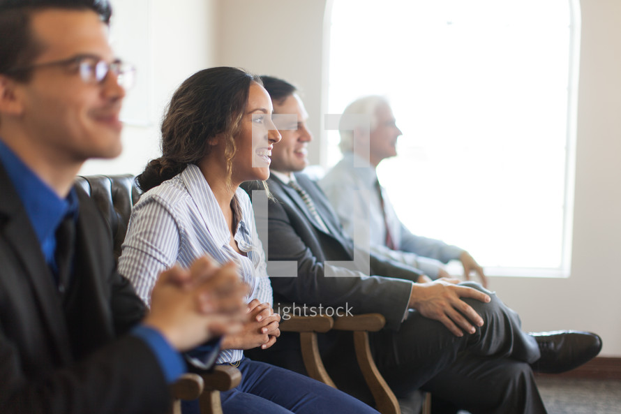 men and women listening to a meeting
